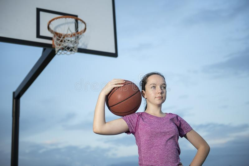 Girl holding a basketball at an outdoor court. Teenage girl holding a basketball at an outdoor court looking off into the distance royalty free stock images