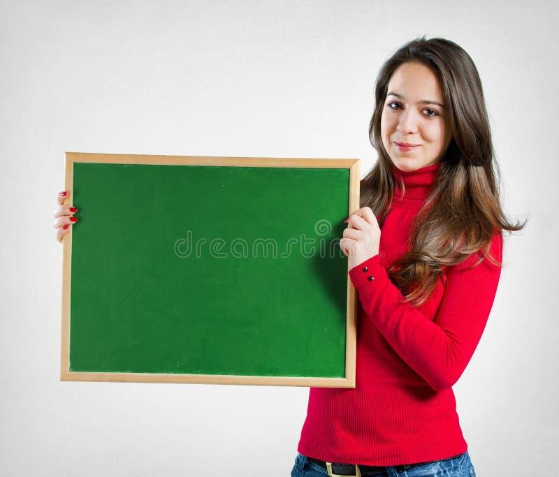 Teenage girl holding a blackboard royalty free stock photography
