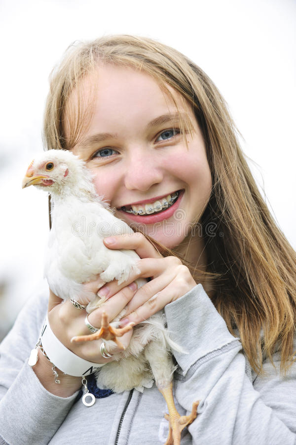 Teenage girl holding chicken royalty free stock photography