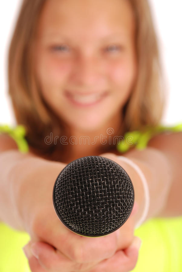 Teenage girl holding a microphone in front. Focus on the microphone. Isolated on white background stock photos