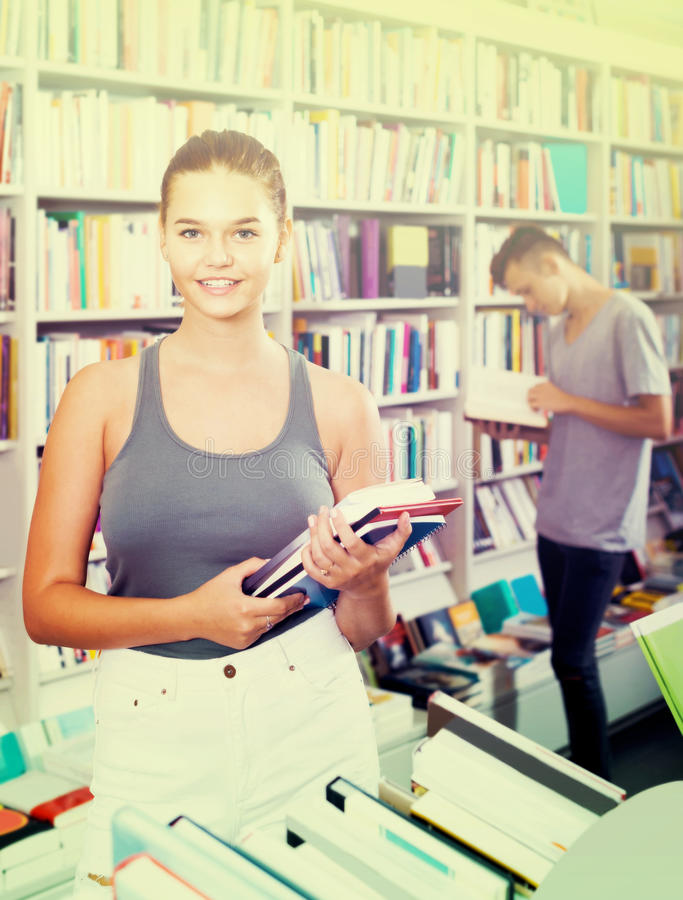 Teenage girl holding new books pile in shop royalty free stock image