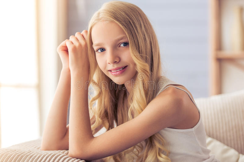 Teenage girl at home. Portrait of pretty blonde teenage girl looking at camera, smiling and leaning on her hands, sitting on sofa at home royalty free stock images