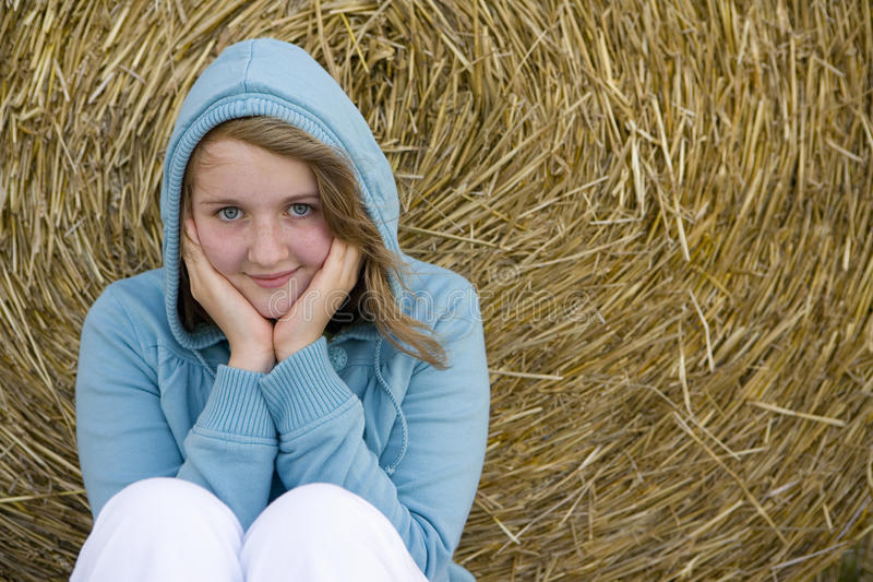 Teenage girl (16-18) in hood by bale of hay, smiling, portrait royalty free stock photo