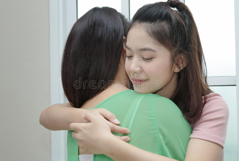 Teenage girl hugging her mom, happy and love family in mother da stock image