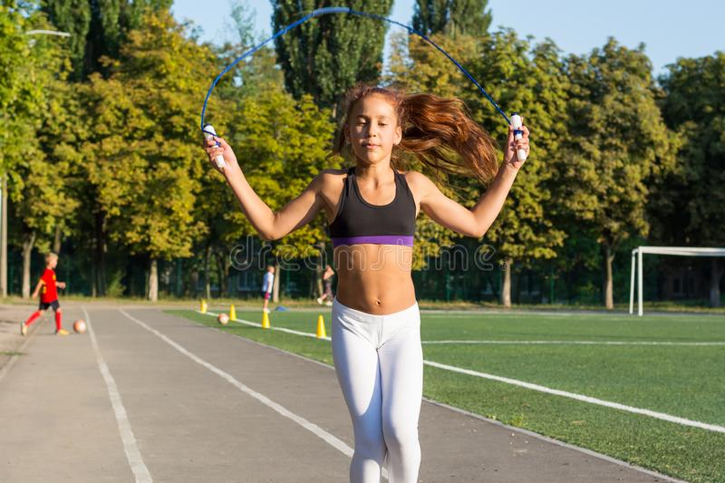 A teenage girl jumping rope in a stadium. stock photo