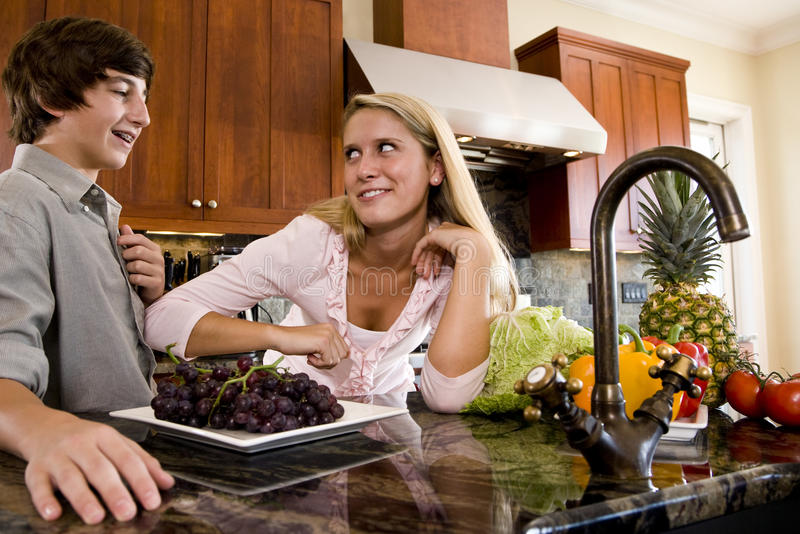 Teenage girl in kitchen talking with brother. Teenage children in kitchen with fruits and vegetables on counter stock images