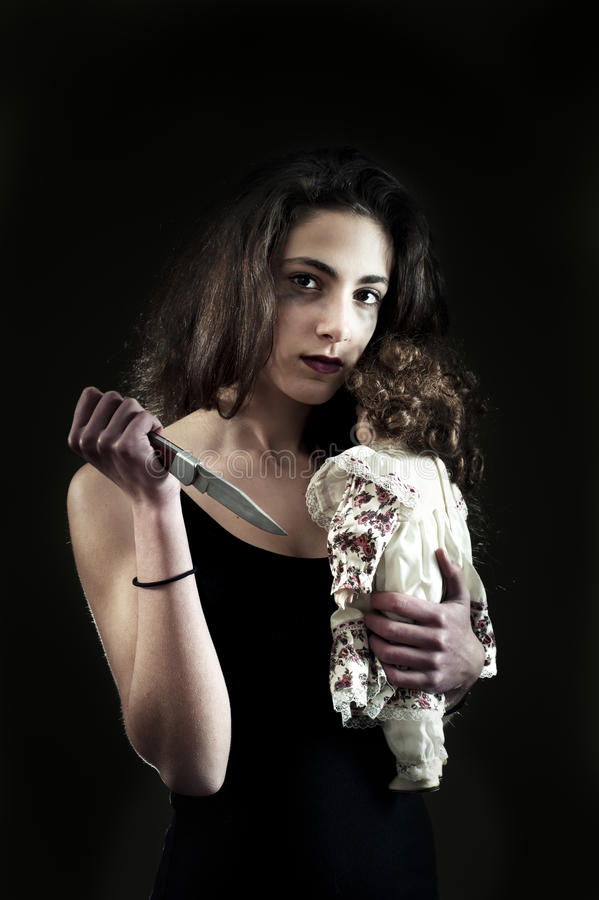 Teenage girl with knife and doll stock photo