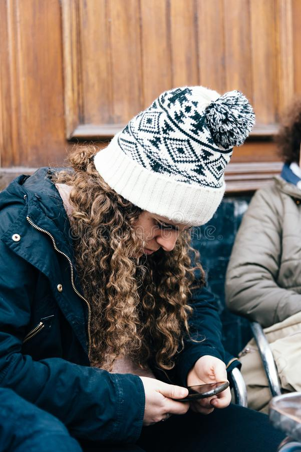 Teenage girl in knit hat texting with cell phone stock image