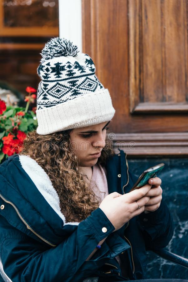 Teenage girl in knit hat texting with cell phone stock photo
