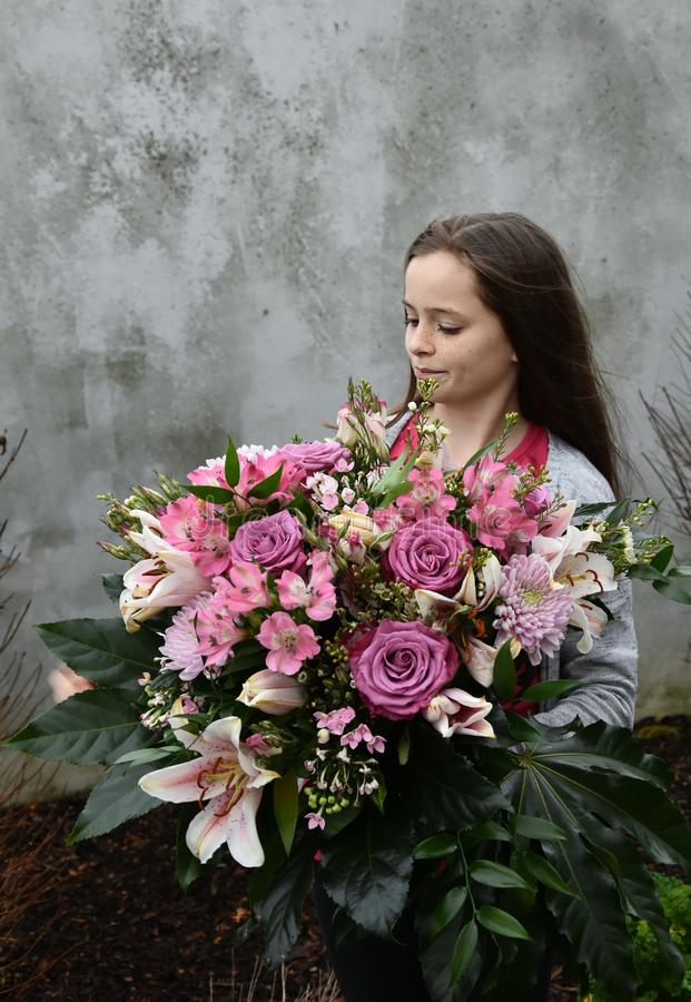 Teenage girl with large bunch of flowers royalty free stock photography