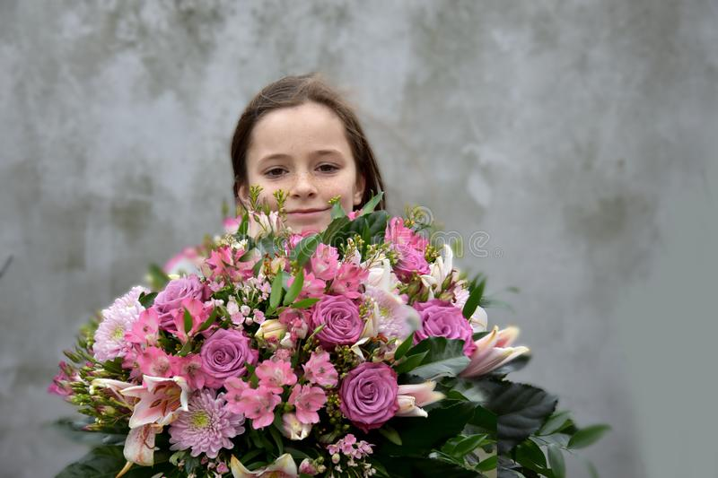 Teenage girl with large bunch of flowers royalty free stock photo