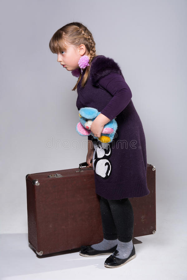 Teenage girl with a large old suitcase. And a plush toy in her hand royalty free stock image