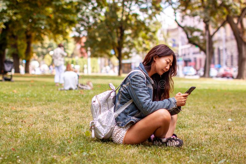 Teenage girl laying in park using mobile phone. Teenage asian girl laying in park using mobile phone in autumn stock photo
