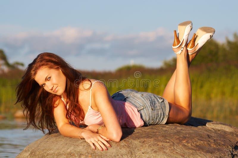 Teenage girl laying on a stone stock image