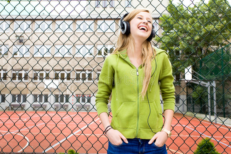 Teenage girl leaning against a chainlink fence royalty free stock images
