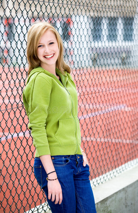 Teenage girl leaning against a chainlink fence royalty free stock photography