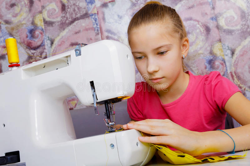 A teenage girl learns to sew stock image