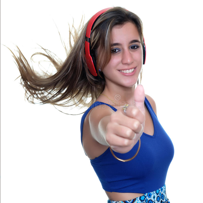 Teenage girl listening to music on wireless headphones isolated. Pretty teenage girl listening to music on wireless headphones and doing a thumbs up sign royalty free stock image