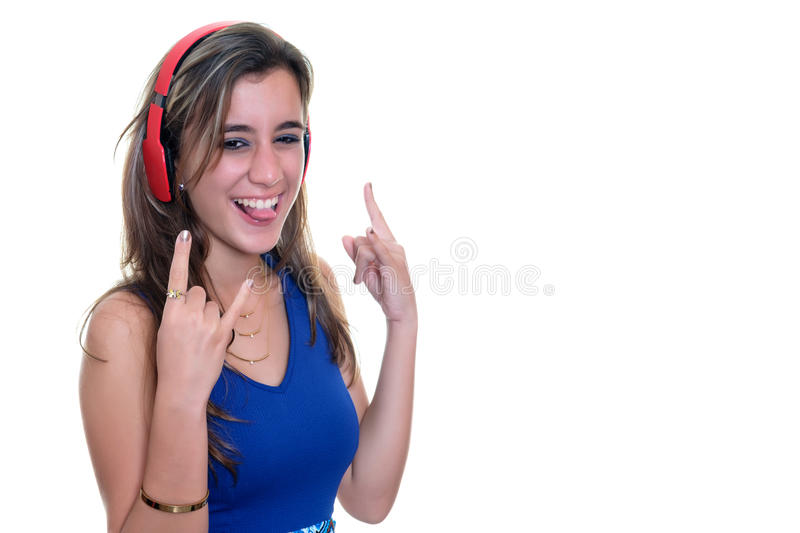 Teenage girl listening to music on wireless headphones isolated. Pretty teenage girl with a playful expression listening to music on wireless headphones royalty free stock images