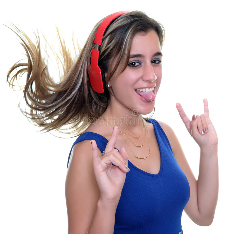 Teenage girl listening to music on wireless headphones isolated. Pretty teenage girl with a playful expression listening to music on wireless headphones stock photography