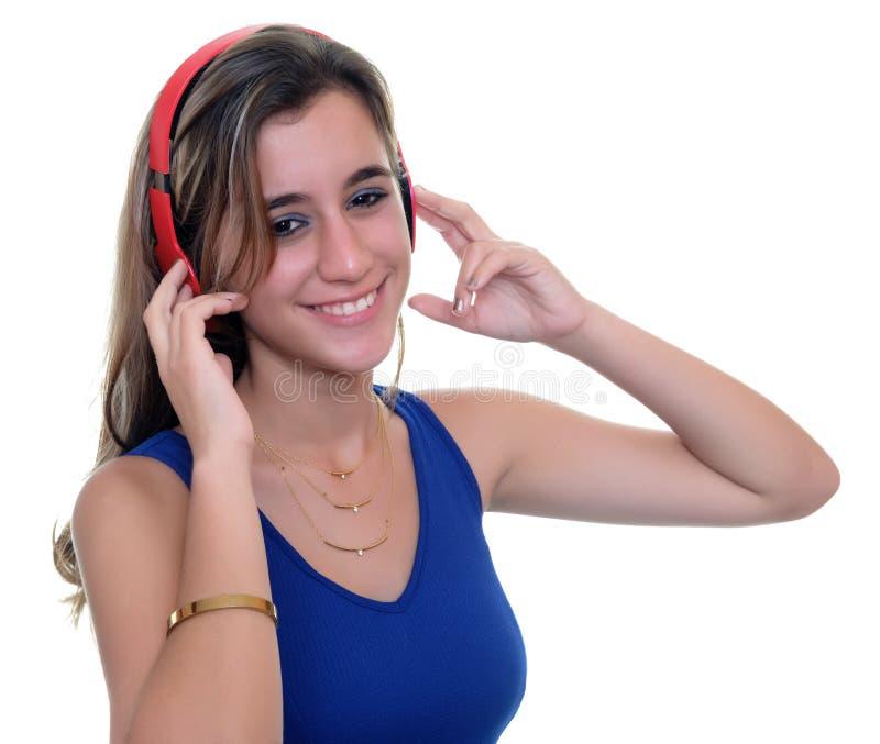 Teenage girl listening to music on wireless headphones isolated. Pretty teenage girl listening to music on wireless headphones - Isolated on white stock image