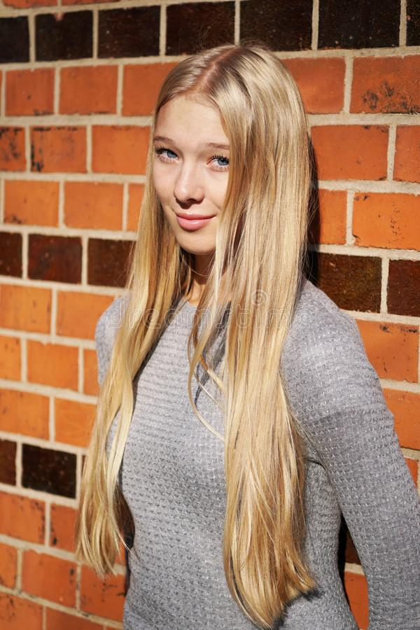 Teenage girl leaning against brick wall royalty free stock photos