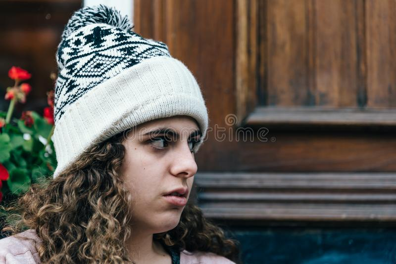 Teenage girl with long and curly hair wearing a knit hat royalty free stock photos