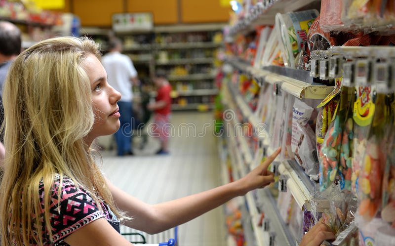 Teenage girl looking at candy. Young blond teenage girl looking at candy or sweets on shelves in a grocery store royalty free stock photography