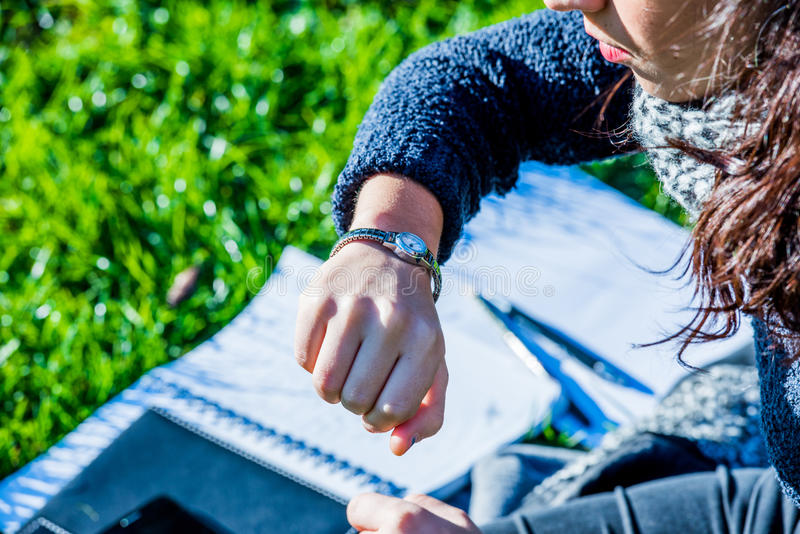 Teenage girl looking at her hand watch - looking the time - close up shot royalty free stock photo