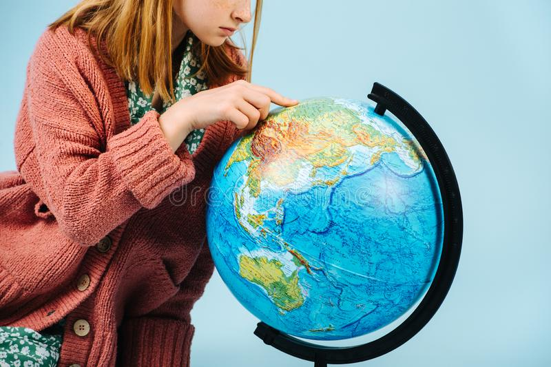Teenage girl looking for her home on a globe. stock photo