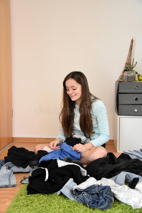 Teenage girl looking for something to wear. Teenage girl sits on the floor looking in the chaos of her clothes. something to wear royalty free stock image