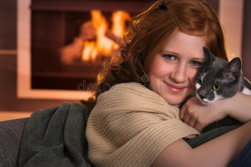 Teenage girl loving cat at home. Teenage girl sitting at fireplace at home cuddling cat smiling royalty free stock photo