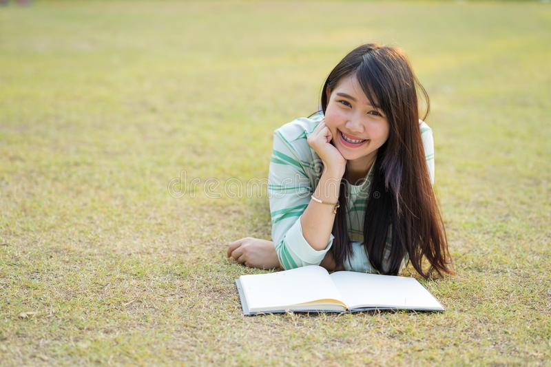 Teenage girl lying down reading a book in lawn at sunset royalty free stock photo