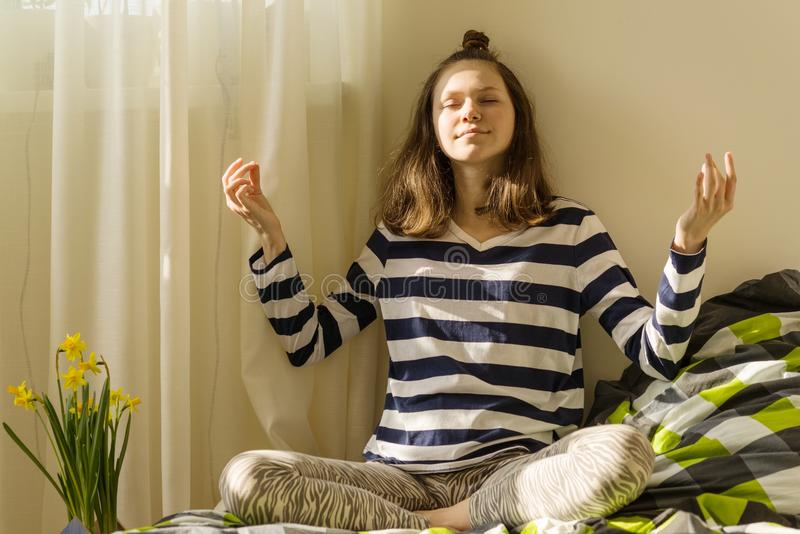 Teenage girl meditating and smiling while sitting in yoga pose on the bed royalty free stock photos