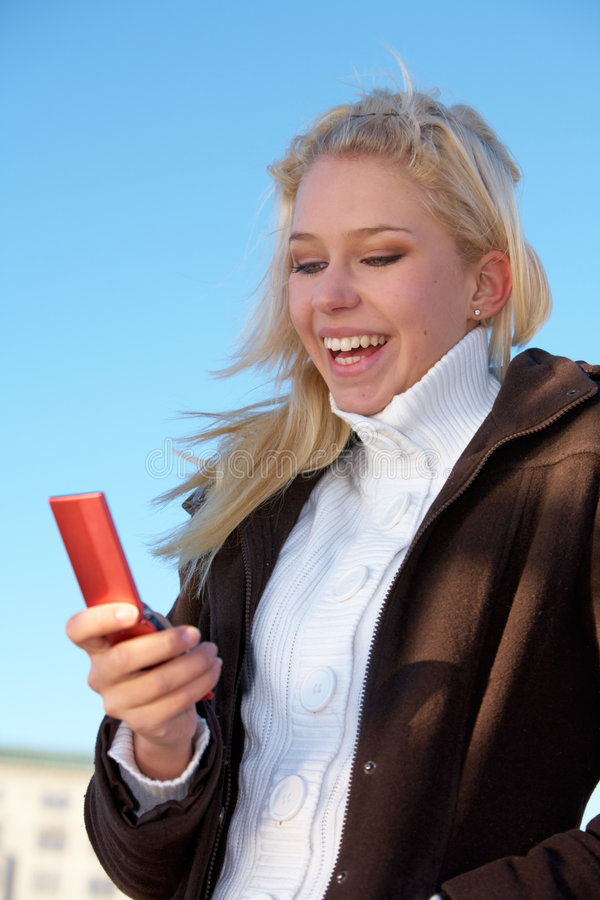 Teenage Girl With Mobile Phone. Teenage girl looking at mobile phone, laughing royalty free stock image