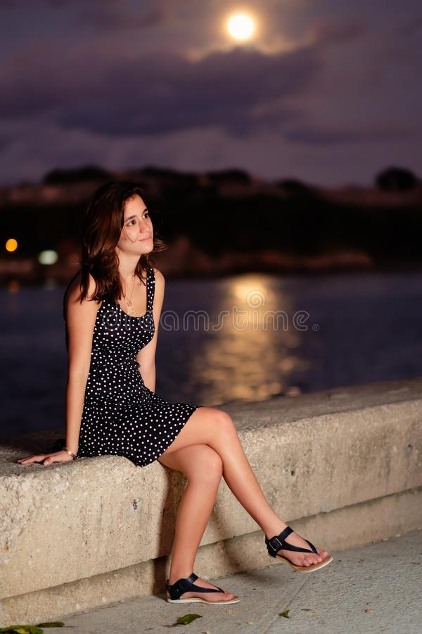 Teenage girl with the moon shining on the ocean in the royalty free stock photos