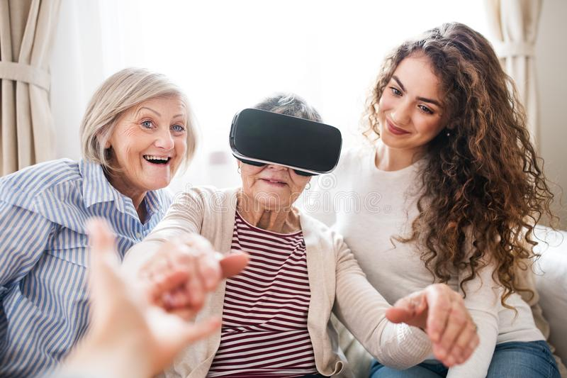 A teenage girl, mother and grandmother with VR goggles at home. A teenage girl, her mother and grandmother with VR goggles at home. Family and generations stock photos