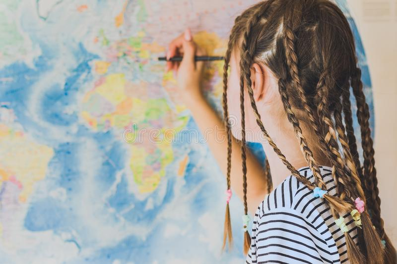 Teenage girl with pigtails makes pencil marks on the world map royalty free stock photo