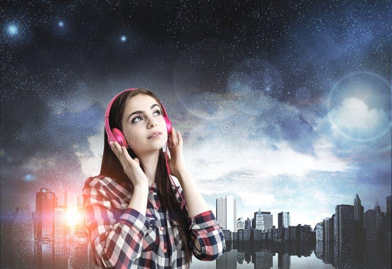 Teenage girl with pink headphones, night city stock photography