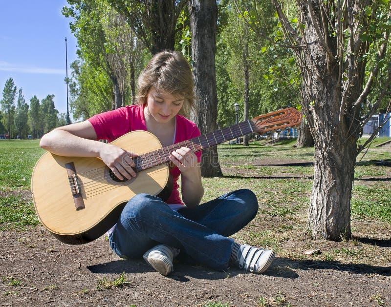 Teenage girl playing guitar stock photography