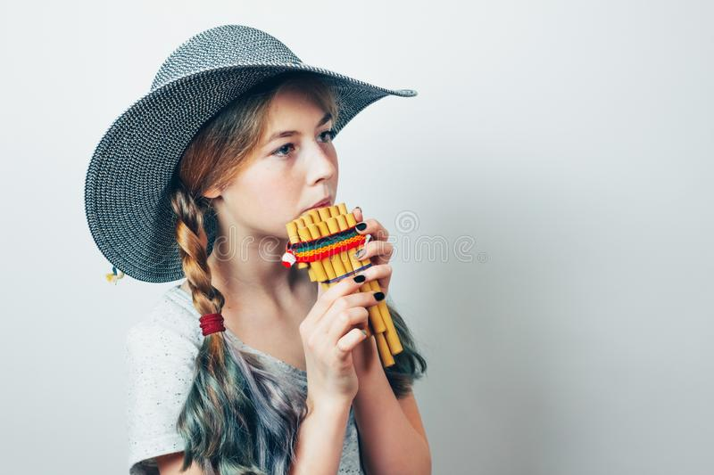 Teenage girl playing  a pan flute. stock photography