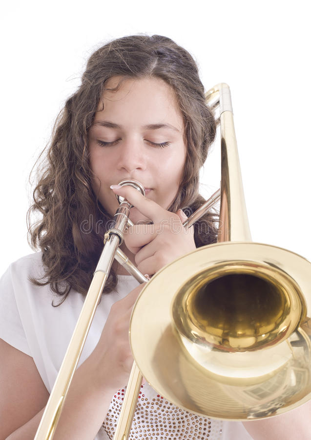 Teenage girl playing the trombone royalty free stock image