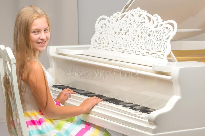 A teenage girl is playing on a white grand piano. The concept of creative personality development, music education, music making on the instrument royalty free stock image