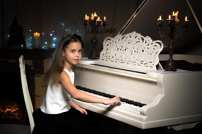 A teenage girl plays a piano on a Christmas night by candlelight stock image