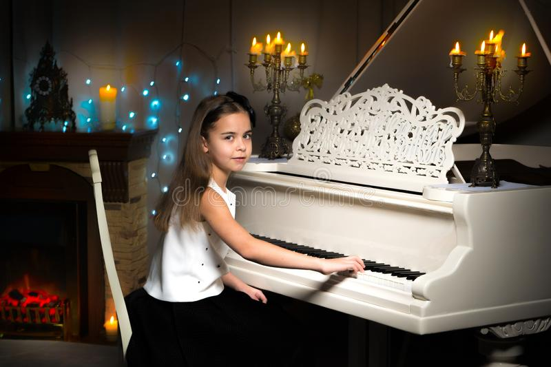A teenage girl plays a piano on a Christmas night by candlelight stock images