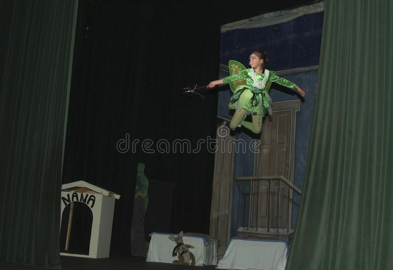 Teenage girl plays tinkerbell in a teen play Peter Pan stock photography