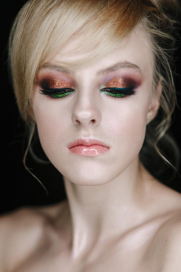 Teenage girl portrait looking down. Beauty Make-up with glitter brown and green eye shadows royalty free stock image