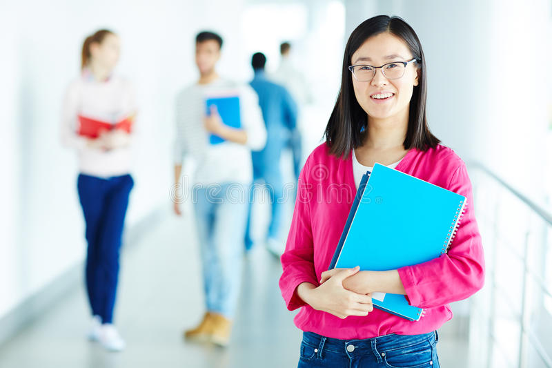 Teenage girl. Portrait of smiling college student holding workbook stock photo