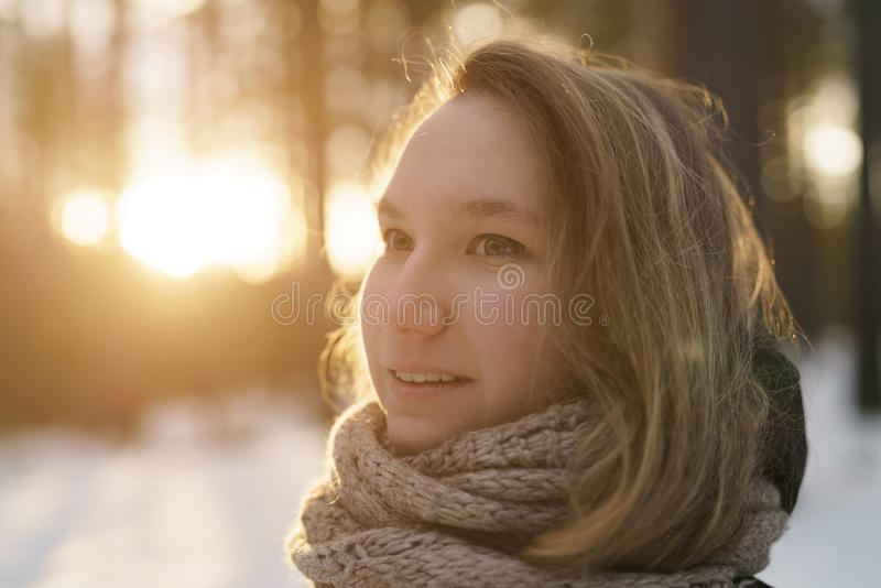 Teenage girl portrait in winter pine forest is sunset royalty free stock photography