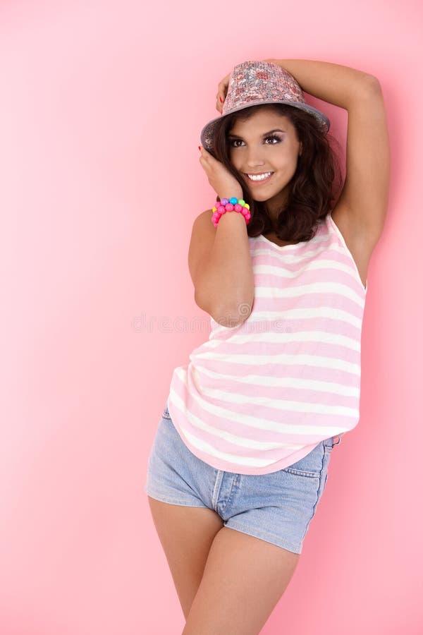 Teenage girl posing over pink background stock photo
